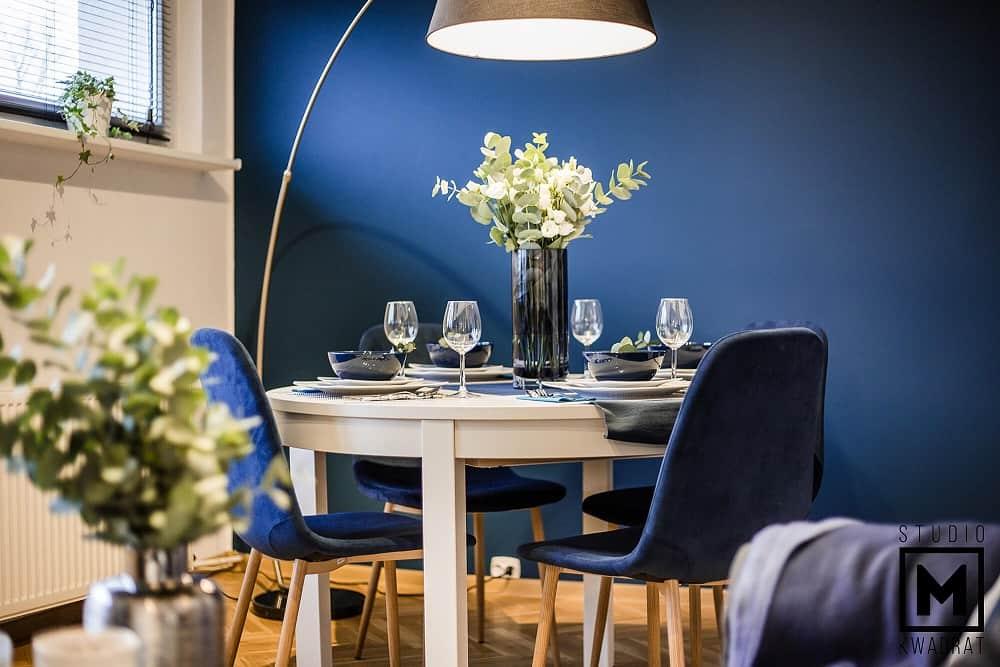 nowoczesny salon w granatowym kolorze, okrąłgły stół z IKEI oraz nieziemska lampa wedka
