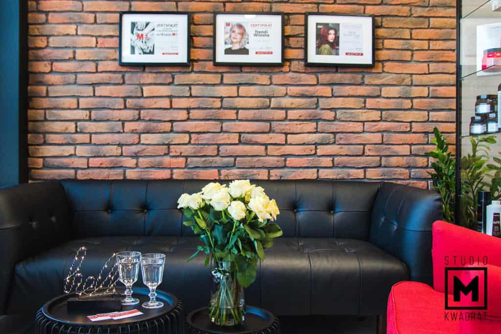 projekt salonu fryzjerskiego w stylu loftowym, poczekalnia z czarną kanapą i ścianą z cegły rozbiórkowej