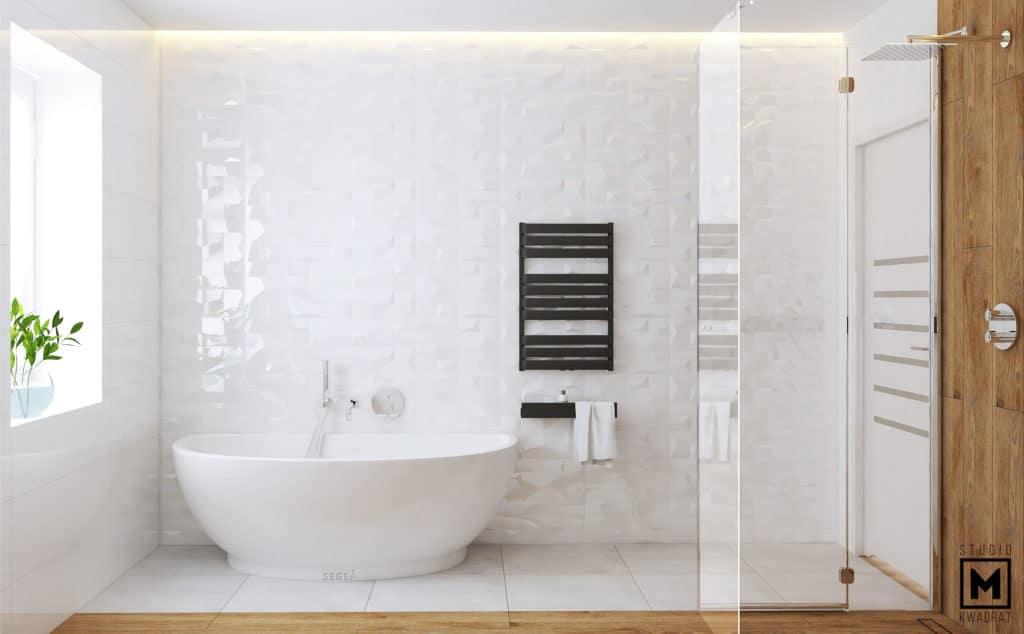 białe płytki 3D w łazience, czarny grzejnik dekoracyjny, biała wanna segea, listwa LED ukryta w suficie podwieszanym