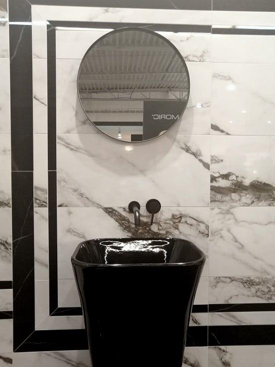 marmur na ścianie i okrągłe lustro kamienna umywalka