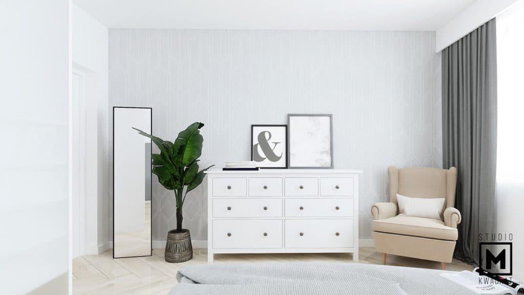 sypialnia małżeńska z beżowym fotelem oraz z białymi meblami i lustrem