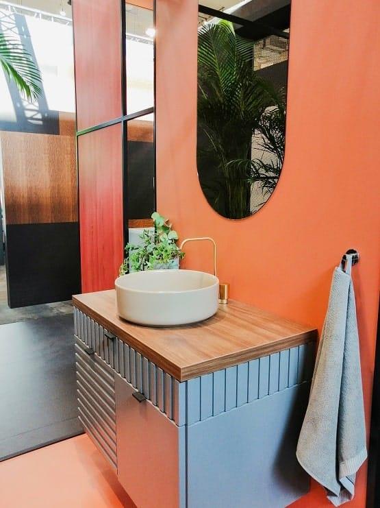 Pomarańczowa łazienka z białą okrągłą umywalką nablatową.