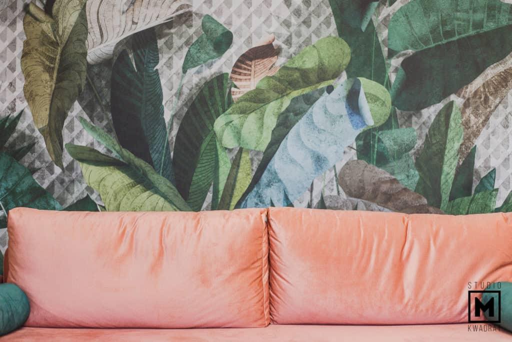 salon kosmetyczny roślinna tapeta i pomarańczowa sofa