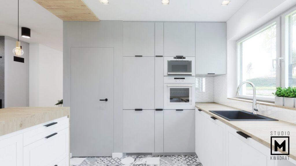 Jasnoszara zabudowa kuchenna i drzwi ukryte do spiżarki.
